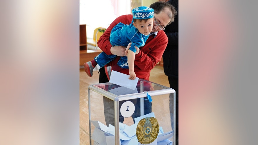 A man helps his son to cast his ballot at a polling station in Astana, the capital of Kazakhstan, Sunday, April 26, 2015. Voters in Kazakhstan turned out in abundance at polling stations Sunday for a presidential election guaranteed to overwhelmingly reconfirm the 74-year-old incumbent, who has ruled over the former Soviet republic for more than 25 years. (AP Photo/Alexei Filippov)