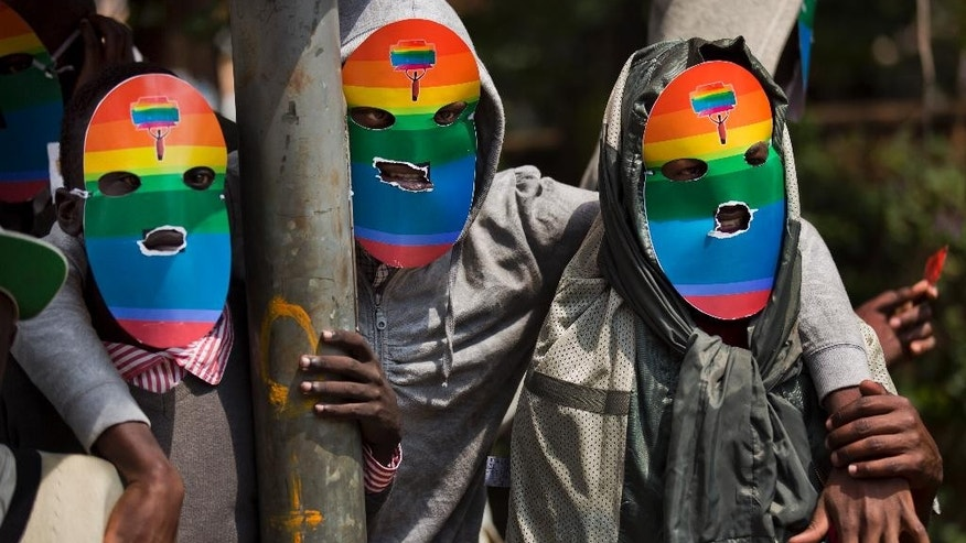 FILE - In this Monday, Feb. 10, 2014 file photo, Kenyan gays and lesbians and others supporting their cause wear masks to preserve their anonymity as they stage a rare protest, against Uganda's tough stance against homosexuality and in solidarity with their counterparts there, outside the Uganda High Commission in Nairobi, Kenya. Kenyan High Court judges on Monday, April 27, 2015 ordered a government agency to register a human rights group representing the country's gay people, a move which had previously been opposed on religious and moral grounds. (AP Photo/Ben Curtis, File)
