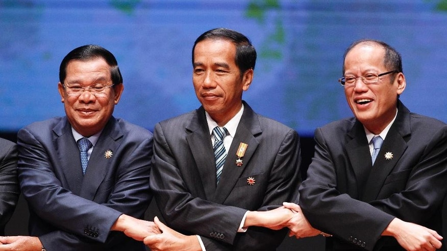 From left to right, Cambodia's Prime Minister Hun Sen, Indonesia's President Joko Widodo, and Philippine's President Benigno Aquino III join their hands during the opening ceremony of the 26th ASEAN Summit in Kuala Lumpur, Malaysia, on Monday, April 27, 2015. (AP Photo/Joshua Paul)