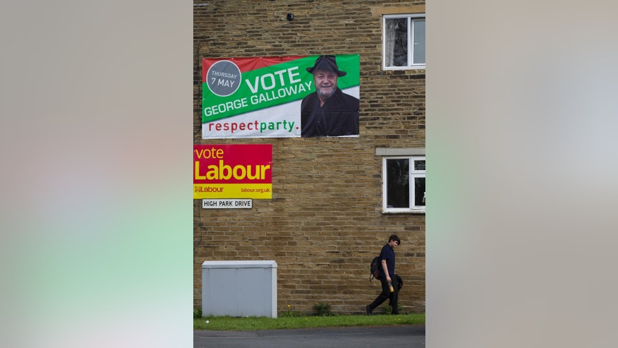 In this photo taken on Wednesday, April 22, 2015,  a person walks past a Labour Party poster, and  a  Respect Party poster,  in the constituency of Bradford West, in Bradford, England,  as Britain's political parties campaign in the lead up to the parliamentary elections on May 7.  Labour candidate Naz Shah is running for Parliament, but she is hardly a typical British politician. She grew up in poverty, fled a teenage forced marriage and campaigned to free her mother, imprisoned for murder after poisoning an abusive partner. Her rival, George Galloway, is a left-wing firebrand who has denounced U.S. senators, saluted Saddam Hussein and once appeared on a reality-TV show pretending to be a cat.  Anyone who thinks Britain's election is dull hasn't been to Bradford West, the campaign's wildest race, where debate ranges from local schools and services to the Israeli-Palestinian conflict, and noble rhetoric collides with character attacks. (AP Photo/Jon Super)