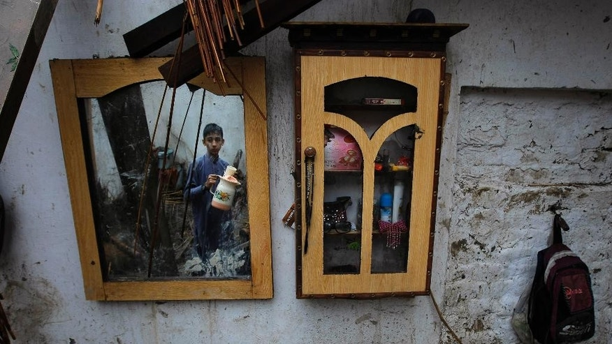 A Pakistani boy collects his belongings from his home that was damaged from heavy rain and windstorm that reached up to a speed of 120 kph (75 mph) Sunday evening which collapsed hundreds of buildings, uprooted trees, and electric poles, in Peshawar, Pakistan, Monday, April 27, 2015. Officials say death toll has risen to at least 44. (AP Photo/Mohammad Sajjad)