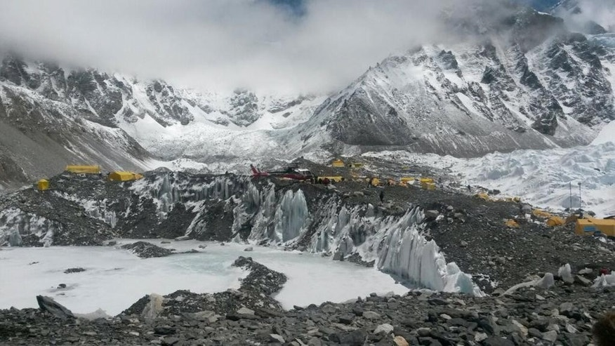 A rescue chopper prepares to land, carrying people from higher camps to Everest Base Camp, Nepal, Monday, April 27, 2015. An avalanche on Saturday, set off by the massive earthquake that struck Nepal, left more than a dozen people dead and dozens more injured. (AP Photo/Nima Namgyal Sherpa)