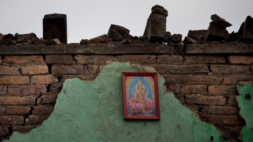 A portrait of Hindu Goddess Lakshmi hangs on the remains of a house that was damaged in Saturday's earthquake, in Kathmandu, Nepal, Monday, April 27, 2015. A strong magnitude earthquake shook Nepal's capital and the densely populated Kathmandu valley on Saturday devastating the region and leaving tens of thousands shell-shocked and sleeping in streets. (AP Photo/Bernat Armangue)