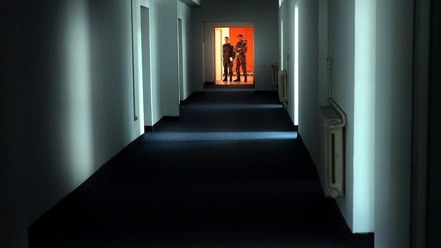 "FILE - In this Wednesday, Nov. 9, 2005, file picture Romanian military staff stand at the end of a corridor on the Mihail Kogalniceanu airbase, near the Black Sea port of Constanta, a Soviet-era facility which became a key focus of a European investigation into allegations that the CIA operated secret prisons, some 250 kilometers (155 miles) east of Bucharest, Romania. Former Romanian president Ion Iliescu has acknowledged approving the CIA's request for a site in Romania, but said he would have refused had he known its destination, one of the CIA ""black sites"" _ prisons outside the U.S. where suspected terrorists were held and subjected to harsh interrogation.(AP Photo/Vadim Ghirda, File)"