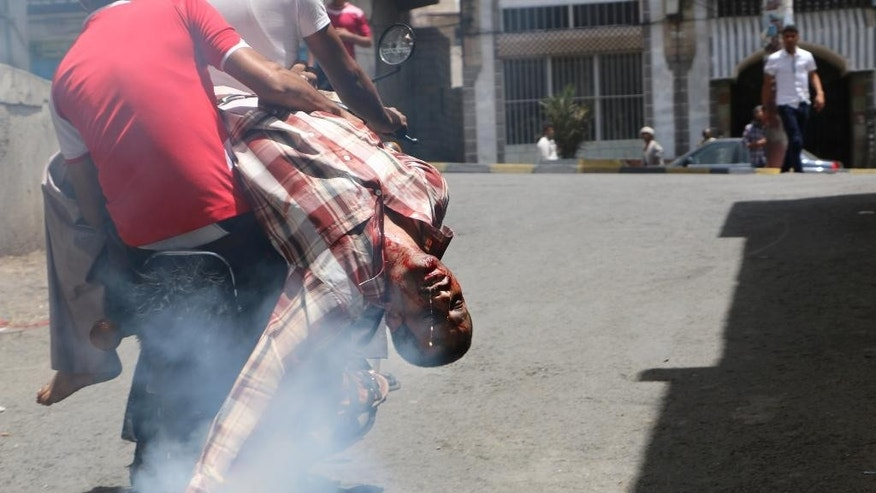 In this Sunday, April 26, 2015 photo, men on a motorbike rush a man who was injured during a crossfire between tribal fighters and Shiite militia known as Houthis, to a hospital, in Taiz, Yemen. The fighting in Taiz between government forces and rebels was heaviest around government and security buildings in the city center, killing some 20 civilians and wounding dozens more, they said, adding that indiscriminately fired mortar rounds hit several private residences and landed near a hospital at one point. (AP Photo/Abdulnasser Alseddik)