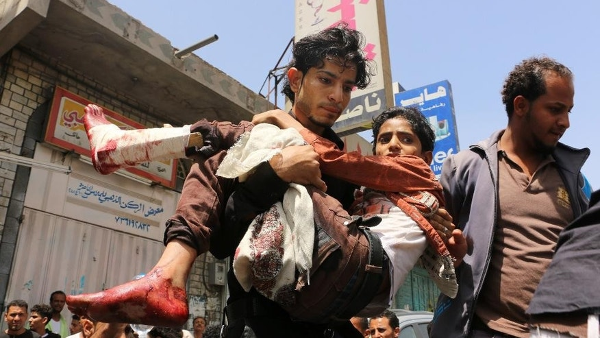 In this Sunday, April 26, 2015 photo, a man carries a boy who was injured during a crossfire between tribal fighters and Shiite militia known as Houthis, in Taiz, Yemen. The fighting in Taiz between government forces and rebels was heaviest around government and security buildings in the city center, killing some 20 civilians and wounding dozens more, they said, adding that indiscriminately fired mortar rounds hit several private residences and landed near a hospital at one point. (AP Photo/Abdulnasser Alseddik)
