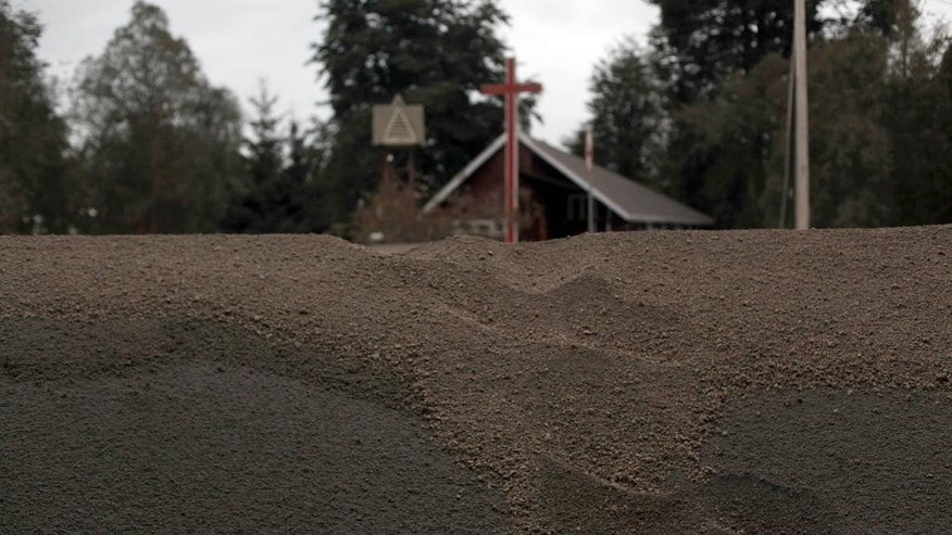 Ash from the eruption of the Calbuco volcano is piled up on the side of a road in Puerto Varas, Chile, Sunday, April 26, 2015. The Calbuco volcano, which had been dormant for more than four decades, had two huge eruptions this week. The head of the National Mining and Geology Service said the volcano's eruptive process could last weeks and even months and warned that a third eruption was possible. (AP Photo/Luis Hidalgo)