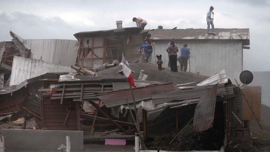 People sweep volcanic ash from the roof of a building in Puerto Varas, Chile, Sunday, April 26, 2015. The Calbuco volcano, which had been dormant for more than four decades, had two huge eruptions this week. The head of the National Mining and Geology Service said the volcano's eruptive process could last weeks and even months and warned that a third eruption was possible. Experts say the volcano has left more than 210 million tons of ash. (AP Photo/Luis Hidalgo)