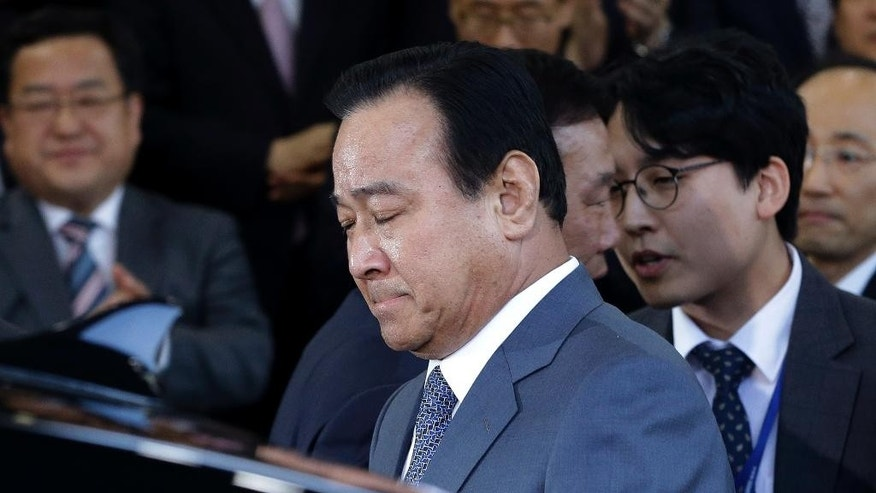 South Korean Prime Minister Lee Wan Koo closes hie eyes as he leaves the Central Government Complex after his farewell ceremony in Seoul, South Korea Monday, April 27, 2015. South Korean President Park Geun-hye on Monday accepted the resignation offer by her prime minister over a bribery scandal. (AP Photo/Ahn Young-joon)