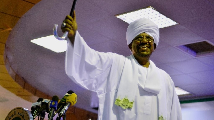 President Omar al-Bashir raises his arm as his supporters cheer at his victory speech after he won the presidential election at the National Congress Party headquarters in Khartoum, Sudan, Monday, April 27, 2015. Al-Bashir won re-election with 94 percent of the vote, according to official results announced Monday, extending his 25-year rule despite international war crimes charges and multiple insurgencies. (AP Photo/Jason Patinkin)