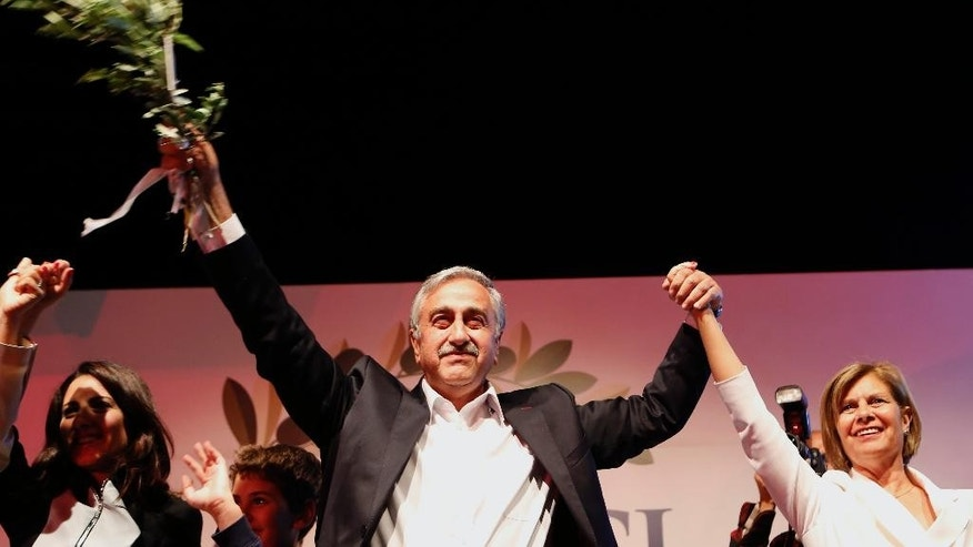 Turkish Cypriot newly elected leader Mustafa Akinci with his wife Miral wave to his supporters after he won the leadership election in Nicosia in the Turkish Cypriot breakaway north part of the divided island of Cyprus, Sunday, April 26, 2015. Akinci, a veteran politician with a strong track record of reaching out to rival Greek Cypriots, was elected as leader of the breakaway Turkish Cypriots in ethnically divided Cyprus. Akinci defeated hard-line incumbent Dervis Eroglu with 60.38 percent of the vote, preliminary official results showed. Turnout for Sunday's vote was just over 64 percent. (AP Photo/Petros Karadjias)