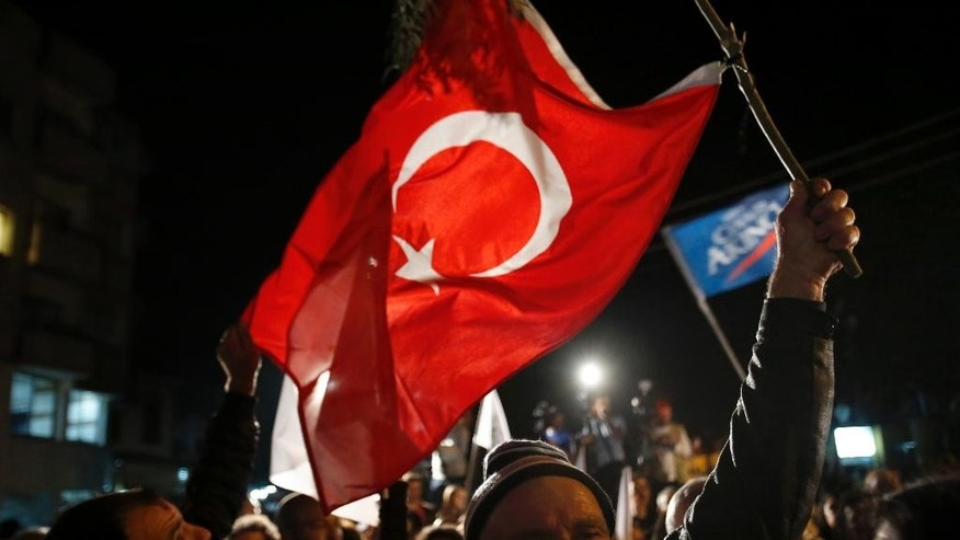 A supporter of Turkish Cypriot newly elected leader Mustafa Akinci celebrates his win as waves a Turkish flag during the Turkish Cypriots election in Nicosia in the Turkish Cypriot breakaway north part of the divided island of Cyprus, Sunday, April 26, 2015. Akinci, a veteran politician with a strong track record of reaching out to rival Greek Cypriots, was elected as leader of the breakaway Turkish Cypriots in ethnically divided Cyprus. Akinci defeated hard-line incumbent Dervis Eroglu with 60.38 percent of the vote, preliminary official results showed. Turnout for Sunday's vote was just over 64 percent. (AP Photo/Petros Karadjias)
