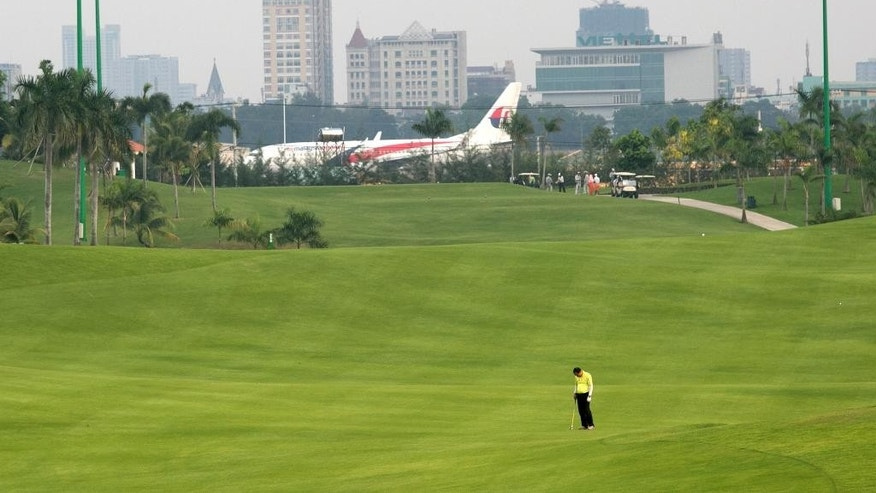 This photo taken April 14, 2015, shows a fairway at Tan Son Nhat Golf Course in Ho Chi Minh City, Vietnam. The course lies on military controlled land, directly beside Vietnam's busiest airport. Top officials in Vietnam's ruling Communist Party have proposed building a new airport about 40 kilometers (25 miles) away. But some city residents and aviation experts say it makes more sense for the airport to expand precisely where the course lies. (AP Photo/Na Son Nguyen)