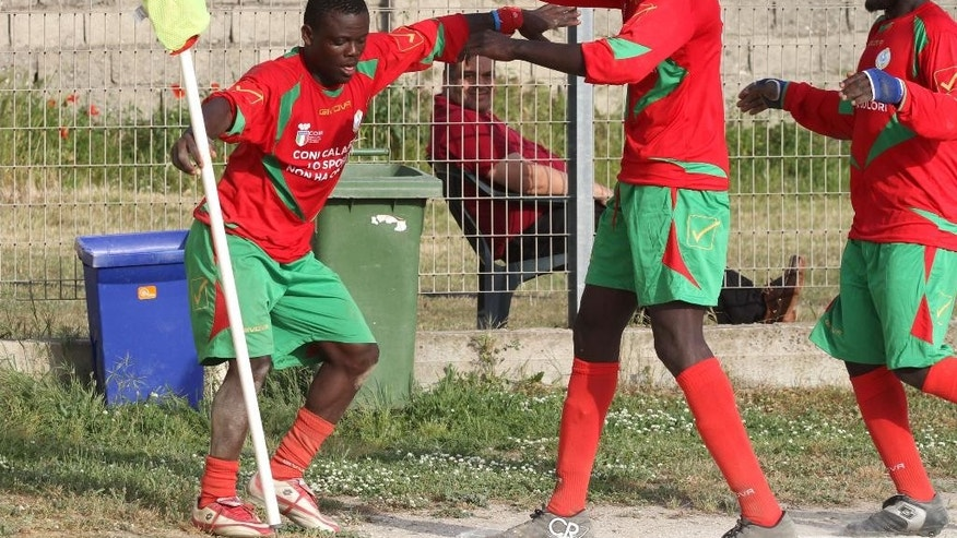 In this picture taken on April 25, 2015 and made available on Tuesday, April 28, 2015, Gordon Kawsi, left, celebrates with his teammates after scoring during a match against Nuova Calimera in San Ferdinando, in the outskirts of Rosarno, southern Italy. A soccer team fielding only African migrants is hoping to win hearts and games in one of Italy's poorest regions, where locals and foreigners once clashed in bloody violence. A local Catholic charity manages the team, Koa Bosco, near Rosarno, Calabria. Hundreds of thousands of migrants in smugglers boats have reached southern Italy in recent years. (AP Photo/Adriana Sapone)