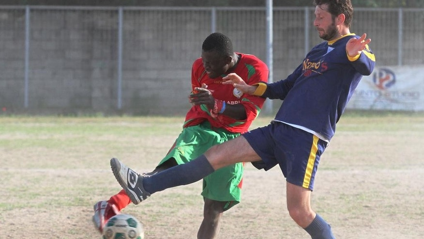 In this picture taken on April 25, 2015 and made available on Tuesday, April 28, 2015, Gordon Kawsi, left, kicks the ball to score during a match against Nuova Calimera in San Ferdinando, in the outskirts of Rosarno, southern Italy. A soccer team fielding only African migrants is hoping to win hearts and games in one of Italy's poorest regions, where locals and foreigners once clashed in bloody violence. A local Catholic charity manages the team, Koa Bosco, near Rosarno, Calabria. Hundreds of thousands of migrants in smugglers boats have reached southern Italy in recent years. (AP Photo/Adriana Sapone)