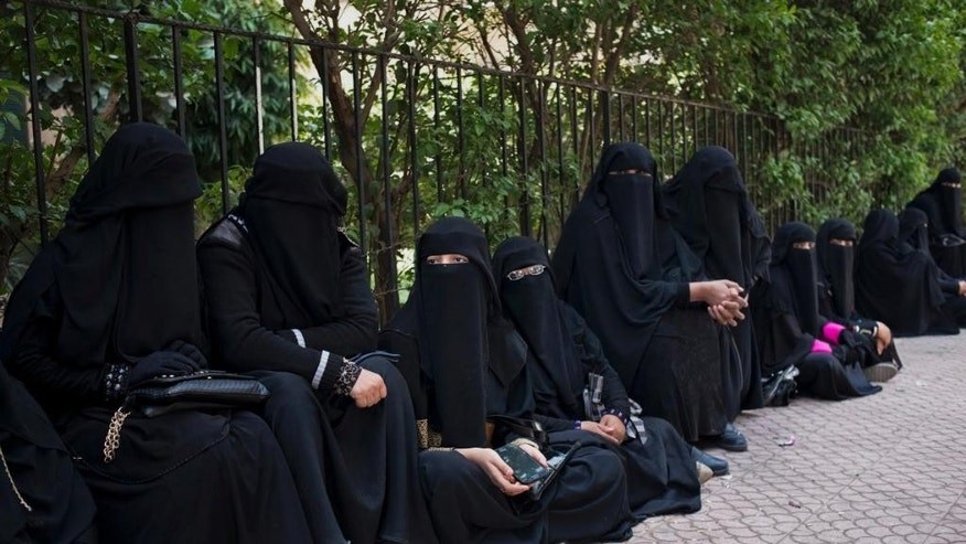 In this Sunday, April 19, 2015 photo shows, Yemeni women wait outside the Yemeni embassy in Cairo, Egypt. As a Shiite rebel offensive and Saudi-led airstrikes rage on in Yemen, thousands of Yemenis remain stuck in Egypt, unable to return home. (AP Photo/Alex Potter)