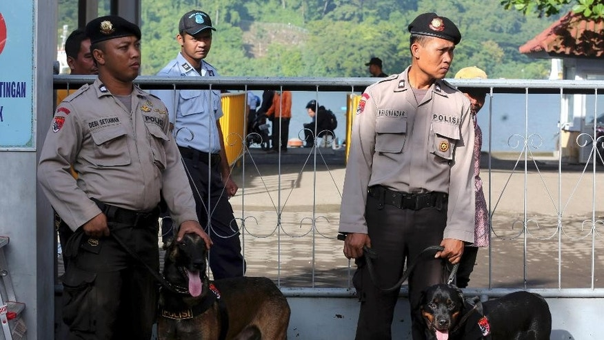 Indonesian police officers with their dogs stand guard at Wijayapura port in Cilacap, Central Java, Indonesia, Monday, April 27, 2015, Indonesia, Tuesday, April 28, 2015. Indonesia notified nine foreigners and a local man convicted of drug trafficking over the weekend that their executions will be carried out within days, ignoring appeals by the U.N. chief and foreign leaders to spare them.  (AP Photo/Tatan Syuflana)