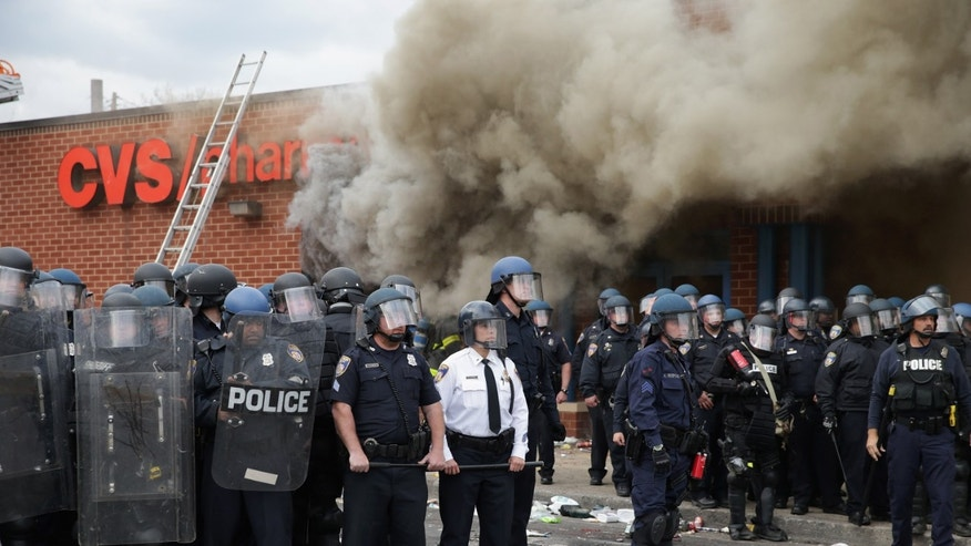 Baltimore Police form a parimeter around a CVS pharmacy that was looted and burned near the corner of Pennsylvania and North avenues during violent protests following the funeral of Freddie Gray April 27, 2015 in Baltimore, Maryland. Gray, 25, who was arrested for possessing a switch blade knife April 12 outside the Gilmor Homes housing project on Baltimore's west side. According to his attorney, Gray died a week later in the hospital from a severe spinal cord injury he received while in police custody.  (Photo by Chip Somodevilla/Getty Images)