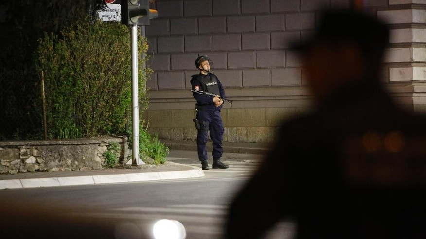 """Police officers secure the area near a police station following a shooting incident in the eastern Bosnian town of Zvornik, 200 Km (124 miles) east of Sarajevo, on Monday, April 27, 2015. Bosnian authorities say a man stormed into a police station in a northeastern town of Zvornik shouting """"Allahu akbar,"""" killing a policeman and wounding two others, according to Police spokeswoman Aleksandra Simojlovic, who confirmed to The Associated Press that the attacker was killed.(AP Photo/Amel Emric)"""