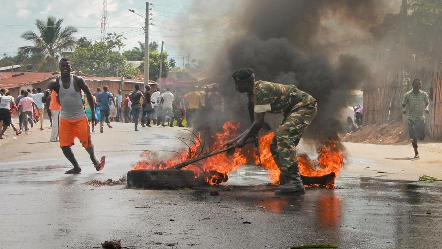 Burundi riot police duck to protect themselves from demonstrators throwing stones during clashes in the Musaga district of Bujumbura, Burundi, Tuesday April 28, 2015. Anti-government street demonstrations continued for a third day after six people died in protests against the move by President Pierre Nkurunziza to seek a third term. (AP Photo/Jerome Delay)