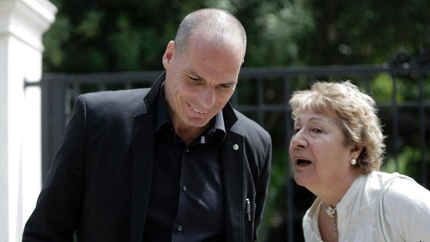 A Greek woman speaks with Greek Finance Minister Yanis Varoufakis as he leaves from a meeting with Greek Prime Minister in Athens, on Tuesday, April 28, 2015.  Varoufakis, who has come under fire from his European peers for dragging his feet in the bailout talks, continued to enjoy the government's support. He will continue to lead the negotiations with the help of Euclid Tsakalotos, who is minister of international financial relations and part of the foreign ministry.(AP Photo/Petros Giannakouris)