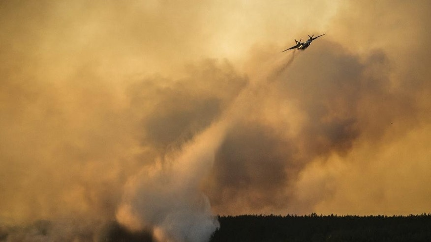 A firework plane extinguishes a forest fire in the Chernobyl area, Ukraine, Tuesday, April 28, 2015. Fire engulfed a large sector of woods in the exclusion zone around the destroyed Chernobyl nuclear power plant Tuesday. Ukrainian Prime Minister Arseniy Yatsenyuk said the fire was the worst in the area for more than two decades, but that the blaze was under control. (AP Photo/Andrew Kravchenko, Pool)