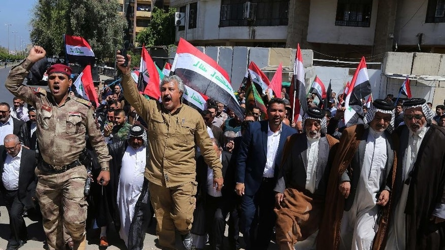 Iraqi Shiites wave the Iraqi flag as they hold a rally to celebrate the Iraqi security forces victory over the Islamic state group in Tikrit, in Baghdad, Iraq, Saturday, April 25, 2015.  The Iraqi government declared victory in Tikrit over extremists of the Islamic State group at the beginning of the month and warned Islamic State fighters holding other Iraqi provinces that they would be the next to fall. (AP Photo/Karim Kadim)