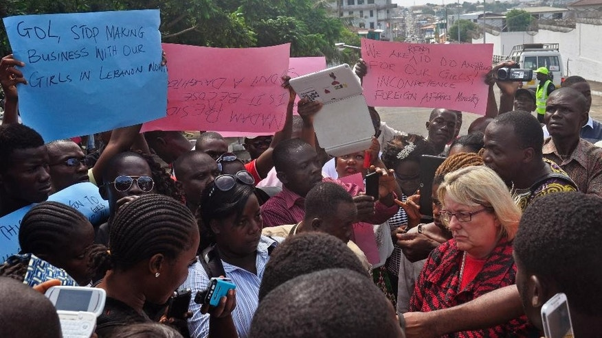 U.S Embassy representative Sally Hodgson, right, collects a petition during a protest near the U.S Embassy in Monrovia, Liberia, Tuesday, April 28, 2015. Protesters gathered Tuesday in front of the U.S. Embassy in Liberia's capital, asking the government to put pressure on Liberian officials to bring back some 60 Liberian young women allegedly trafficked into Lebanon between 2011 and 2012. U.S. Embassy Public Affairs director Sally Hodgson said the embassy received the petition and they were already engaged with the Liberian authorities. (AP Photo/Abbas Dulleh)