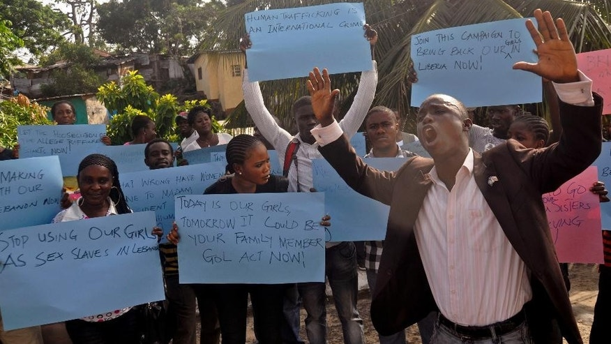 People protest near the U.S Embassy against the alleged trafficking of Liberian woman in Monrovia, Liberia, Tuesday, April 28, 2015. Protesters gathered Tuesday in front of the U.S. Embassy in Liberia's capital, asking the government to put pressure on Liberian officials to bring back some 60 Liberian young women allegedly trafficked into Lebanon between 2011 and 2012. (AP Photo/Abbas Dulleh)