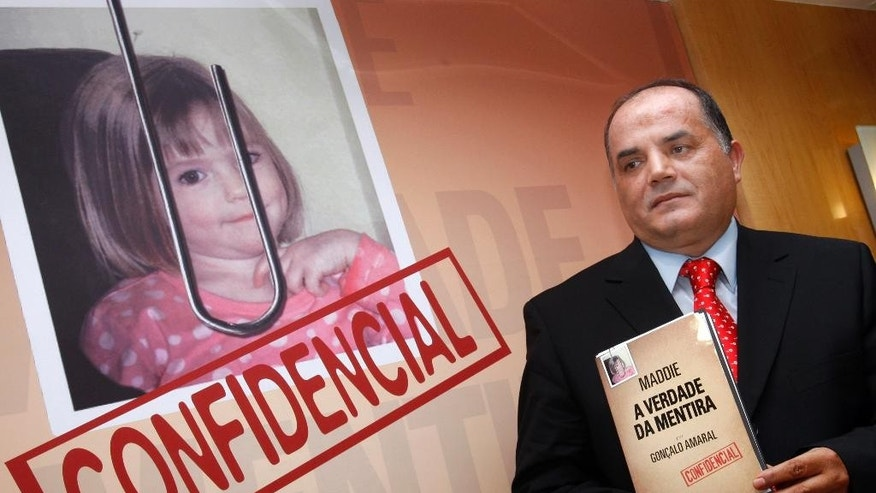 "July 24 2008: Former detective Goncalo Amaral poses with his book whose title translates as ""The Truth in the Lies"" during its launch in Lisbon."