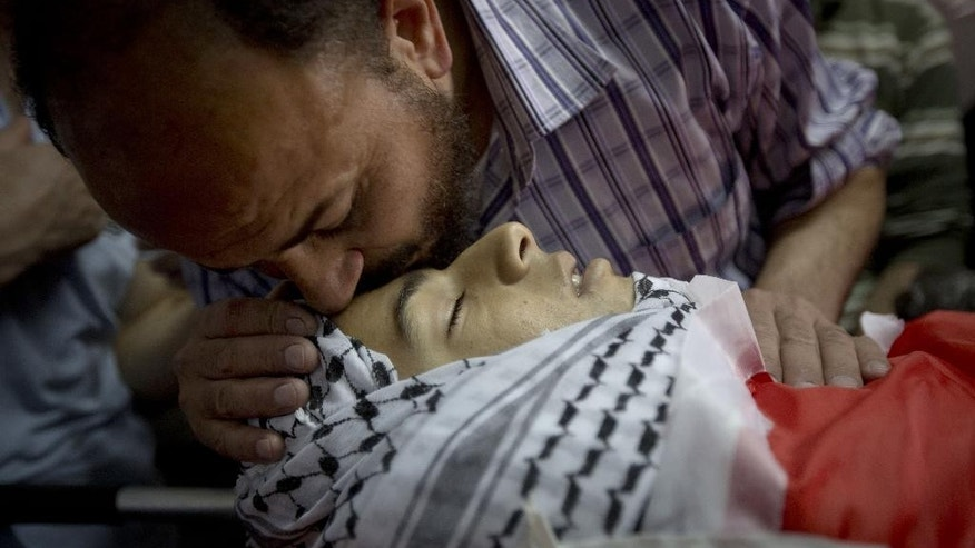 A Palestinian man kisses the forehead of  Mohammed Yehya, who died from wounds in clashes with Israeli troops the night before, during his funeral procession, in the al-Araqa village in the west bank city of Jenin, Tuesday, April 28, 2015. The officials say Yehya died on Tuesday at a hospital in the West Bank city of Nablus. Palestinians say he was shot in the abdomen the on Monday night after hurling rocks at Israeli troops. (AP Photo/Majdi Mohammed)