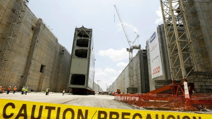 Caution tape keeps unauthorized personnel away as employees work on the Panama Canal expansion project new set of locks while the last rolling gate is installed in Cocoli, near Panama City, Tuesday, April 28, 2015. The Panama Canal Authority supervised the installation of the last of 16 giant lock gates that are a key part of the waterway's multibillion-dollar expansion. The construction of the third set of locks will allow the passage of Post-Panamax vessels or container ships much too big to fit through the Panama Canal's old locks. (AP Photo/Arnulfo Franco)