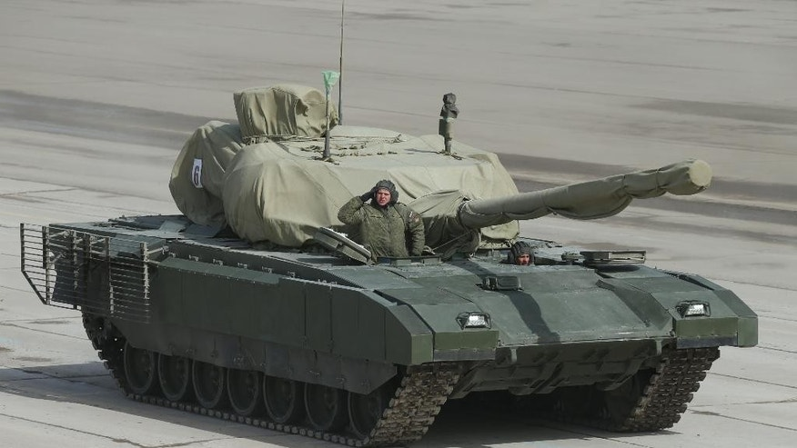 This photo taken Monday, April  13, 2015, shows the T-14 Armata tank, with its turret covered with fabric, during a rehearsal for the Victory Day parade at a shooting range outside Moscow, Russia. The Russian Defense Ministry has released photographs of its new tank, which is to be shown to the public for the first time during the Victory Day parade on Red Square next month. The tank is said to surpass all Western versions because of its remotely controlled cannon and the protection it offers its crew. (Vadim Savitsky/Russian Defense Ministry via AP)