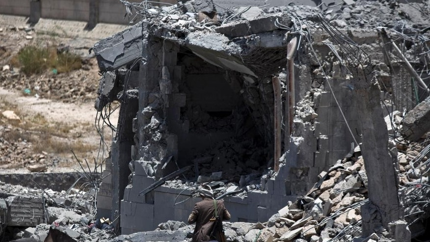A Shiite fighter, known as a Houthi, collects ammunition at the residence of a military commander of the Houthi militant group, destroyed by a Saudi-led airstrike, in Sanaa, Yemen, Tuesday, April 28, 2015. A security official in Saudi Arabia says a soldier has been killed and another wounded in a gunfight with Shiite Houthi rebels along the kingdom's southern border with Yemen. (AP Photo/Hani Mohammed)