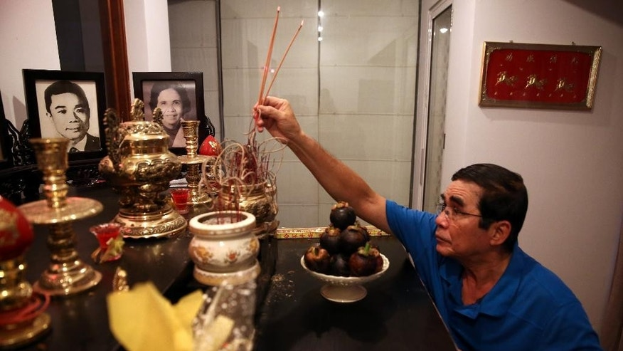 In this photo taken on April 20, 2015, Lu Dinh Trieu, who served in the South Vietnamese Army, burns incense to pay tribute to his ancestors at his house in Ho Chi Minh City, Vietnam. When Luu Dinh Trieu was drafted into the South Vietnamese army in 1972, he went to war against his father, Luu Qui Ky, in left picture on altar, who was a top official in the Communist Party's propaganda unit. Their divide was in essence the divide between north and south: slow to heal, despite the appearances of a unified country moving beyond its bloody past. (AP Photo/Na Son Nguyen)
