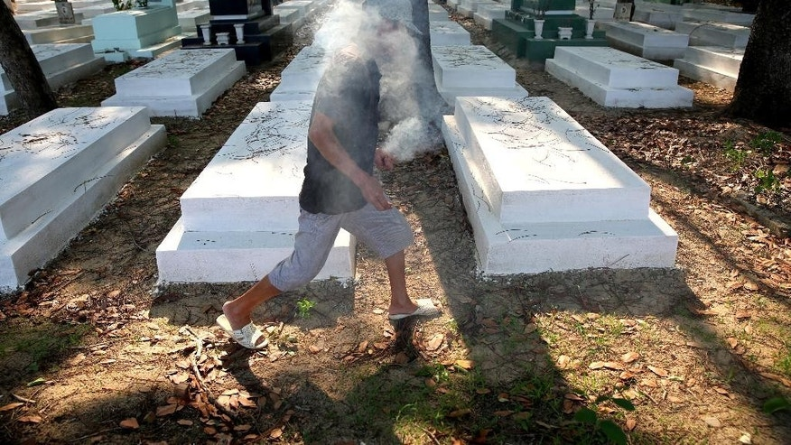"In this photo taken on April 18, 2015, Nguyen Van Ba helps visitors place sticks of incense into graves at the former South Vietnamese military cemetery, in Binh Duong province, outside of Ho Chi Minh City, Vietnam. The cemetery houses up to 18,000 graves and is a tangled mess of leaves and overgrown weeds, strewn trash, broken headstones and mounds of dark earth with missing or broken markers. In Vietnamese high school textbooks, the war is explained as ""resistance against the Americans for national salvation,"" and the South Vietnamese military is referred to in some places as the ""henchmen army."" There is nothing written about why the south was fighting or what it hoped to achieve. (AP Photo/Na Son Nguyen)"