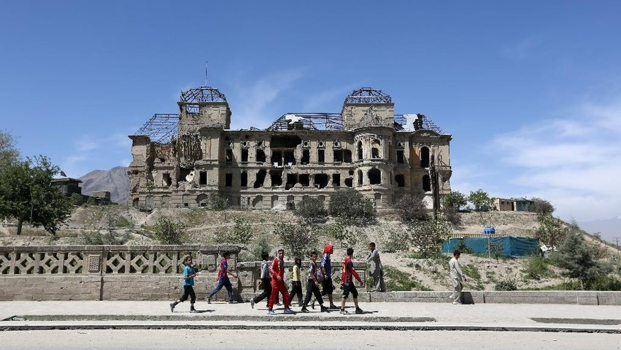 Afghan boys walk past the palace of the late King Amanullah Khan, which was destroyed during the civil war in early 1990s, in Kabul, Afghanistan, Tuesday, April 28, 2015. (AP Photo/Rahmat Gul)