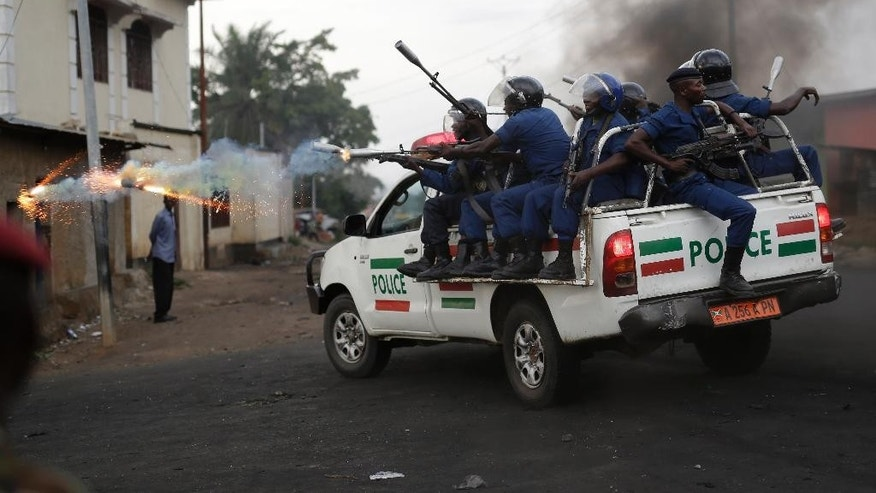 Burundi riot police fire tear gas as they chase demonstrators during clashes in Bujumbura, Burundi, Wednesday April 29, 2015. Protesters were again on the streets Wednesday, angry over the Burundian president's third term bid that they say is unconstitutional as a top U.S. diplomat headed to the East African nation. (AP Photo/Jerome Delay)