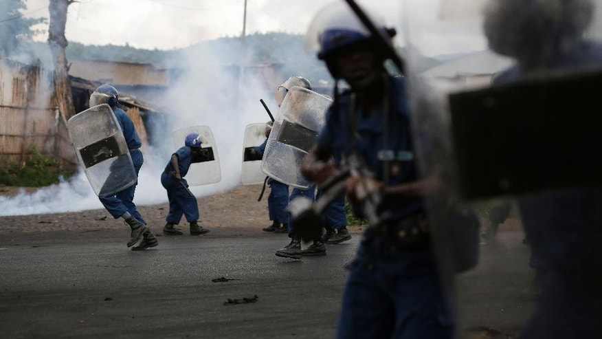 Burundi riot police using tear gas give chase to demonstrators during clashes in Bujumbura, Burundi, Wednesday April 29, 2015. Protesters were again on the streets Wednesday, angry over the Burundian president's third term bid that they say is unconstitutional as a top U.S. diplomat headed to the East African nation. (AP Photo/Jerome Delay)