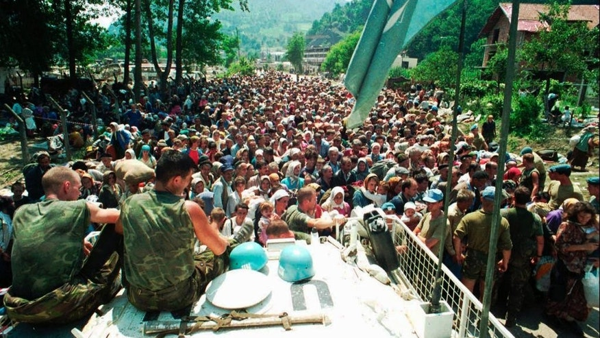 FILE - In this July 13, 1995 file photo Dutch UN peacekeepers sit on top of an APC while Muslim refugees from Srebrenica, eastern Bosnia, gather in the village of Potocari, some 5 kms north of Srebrenica. A Dutch high court has ruled on Wednesday, April 29, 2015 that retired General Thom Karremans could not be held criminally liable on grounds of command responsibility. The military chamber of the Arnhem court ruled that Karremans who commanded Dutch peacekeepers in the Bosnian enclave of Srebrenica when Bosnian Serb fighters overran the town and massacred some 8,000 Muslim men should not be prosecuted for involvement in the slayings. (AP Photo, File)
