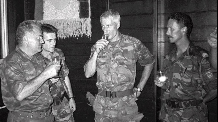 FILE - In this July 12, 1995 file photo Bosnian Serb army General Ratko Mladic, left, drinks with Dutch military Col. Thom Karremans, second right, in the Bosnian village of Potocari. A Dutch high court has ruled on Wednesday, April 29, 2015 that retired General Thom Karremans could not be held criminally liable on grounds of command responsibility. The military chamber of the Arnhem court ruled that Karremans who commanded Dutch peacekeepers in the Bosnian enclave of Srebrenica when Bosnian Serb fighters overran the town and massacred some 8,000 Muslim men should not be prosecuted for involvement in the slayings. (AP Photo, File)