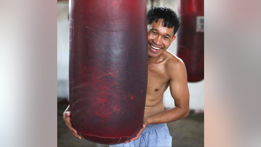"In this April 21, 2015, photo, retired Filipino boxer and now trainer Rexon Flores poses inside a boxing gym in suburban Paranaque, south of Manila, Philippines. Flores, 33, said, ""They all want to be champions ... but the most important thing is to not be swell-headed. If you become swell-headed, your boxing skills will suffer. You will just fool around and you will lose focus on boxing. ""Discipline is primary. If you don't have discipline, all your dreams will just flow away like water."" (AP Photo/Aaron Favila)"