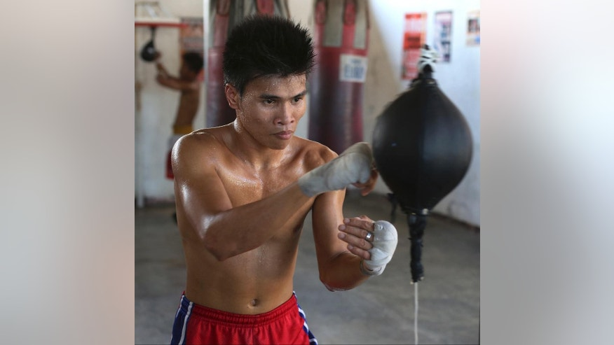 "In this April 22, 2015, photo, Filipino boxer Rolly Macaso poses inside a boxing gym in suburban Paranaque, south of Manila, Philippines. Macaso, 21, a former laborer and baker who once scavenged garbage heaps for recyclables, and now hopes boxing leads him to a better life, said, ""I want to be like Manny so I could help my parents, to lift them out of poverty... Just one (title) belt would be enough for me. That's my dream, to be a world boxing champion... If I get the belt, the money will just come with it."" Manny Pacquiao's rise from crushing poverty to global fame and fortune has inspired a whole generation of Filipino fighters, who look up to his legend as their dream and boxing as a ticket out of harsh lives and uncertainties. (AP Photo/Aaron Favila)"