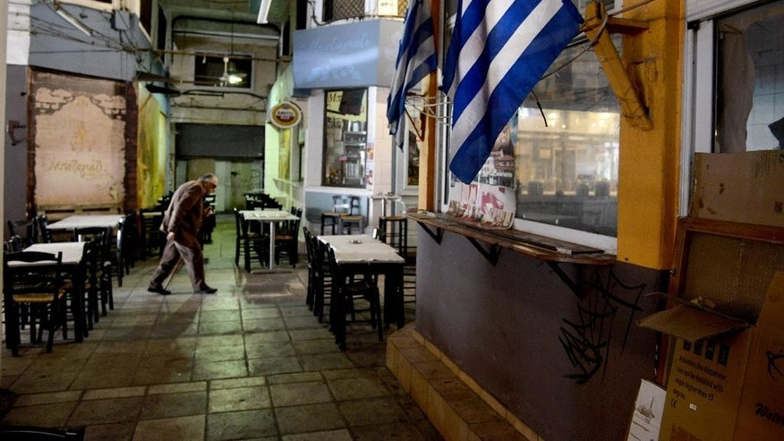 A man walks past a Greek flag in the central market of the northern port city of Thessaloniki , Greece, Wednesday, April 29, 2015. Greece is to present a draft bill of reforms to creditors Wednesday in the hope it will earn their approval and pave the way for the unlocking of vitally needed bailout funds. (AP Photo/Giannis Papanikos)