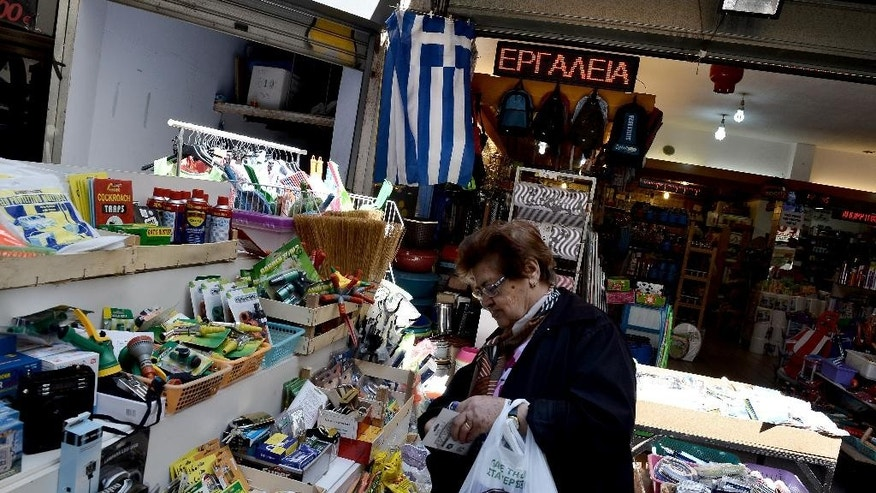 A woman checks products inside a shop at the northern port city of Thessaloniki, Greece, Wednesday, April 29, 2015. Greece says it will discuss with its creditors on Thursday a draft bill of reforms it hopes will earn their approval and pave the way for the unlocking of vitally needed bailout funds.  (AP Photo/Giannis Papanikos)