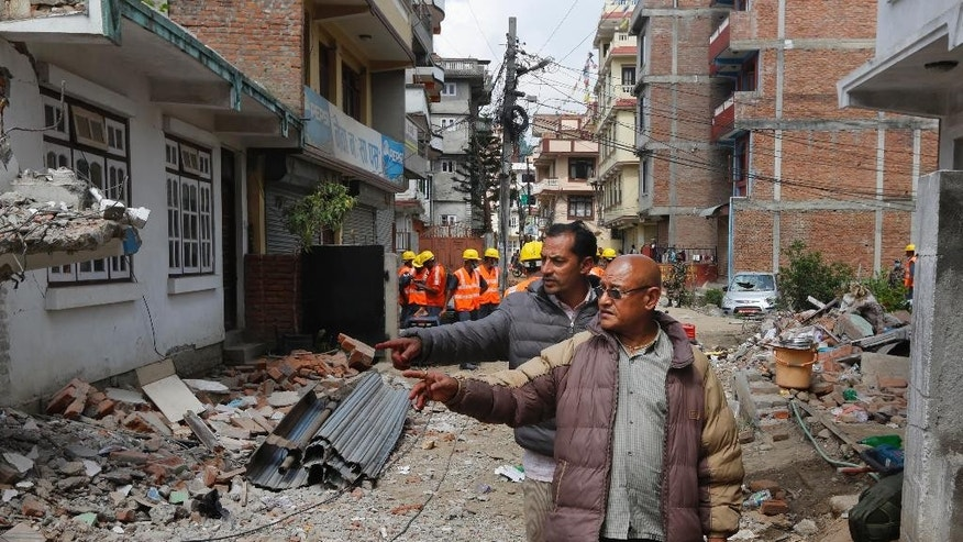 In this Tuesday, April 28, 2015 photo, Shankar Pradhan, left, and his older brother Bharatman Pradhan look at Bharatman's house collapsed by Saturday's massive earthquake in Kathmandu, Nepal. When the quake crumpled their four-story house into a cloud of dust April 25, a total of 18 family members were killed in the building. About 30 of his relatives had gathered in the house for a weeklong traditional Hindu prayer session he said was meant to beget peace and safety. At 11:56 a.m., the house began shaking. About a dozen people had managed to flee in time. (AP Photo/Manish Swarup)