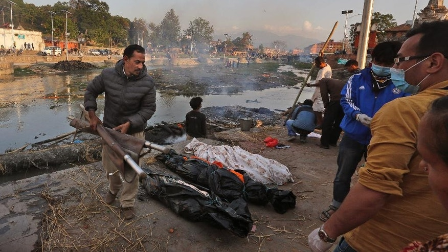In this Tuesday, April 28, 2015 photo, Shankar Pradhan, left, brings bodies of his family members who died in Saturday's massive earthquake for cremation at a ghat on the banks of Bagmati River near the Pashupatinath Temple in Kathmandu, Nepal. The ancient Hindu cremation rite is meant to purify souls for the afterlife, and this was far from the only one for Pradhan and his extended family. When the quake crumpled his brother's four-story house into a cloud of dust on April 25, it left them with a total of 18 souls to prepare. (AP Photo/Manish Swarup)