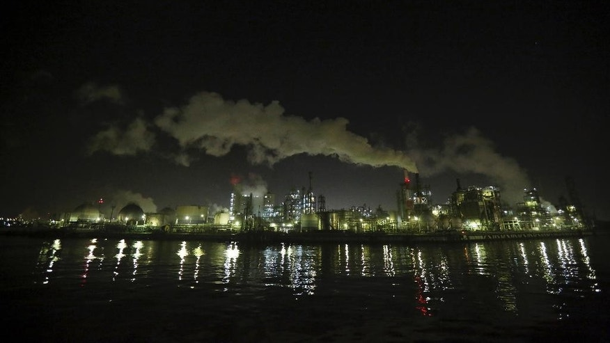In this Nov. 29, 2014 photo, an industrial zone is seen at night in Kawasaki, south of Tokyo. Japan's industrial production fell in March, 2015, but by less than forecast, casting doubt on expectations that the central bank will opt to expand its already lavish monetary stimulus. The government said Thursday, April 30, 2015 that industrial production fell 1.2 percent in March from a year earlier and 0.3 percent from the month before.  (AP Photo/Eugene Hoshiko)
