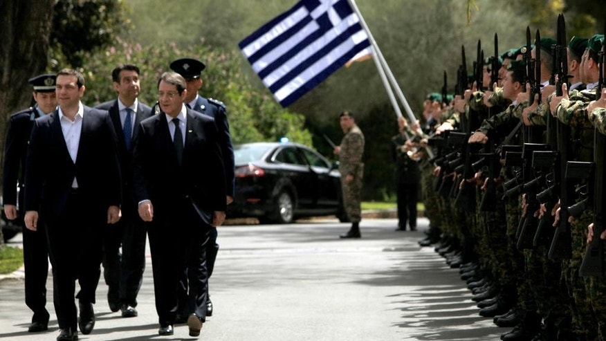 Greek Prime Minister Alexis Tsipras, left, escorted by Cyprus' President Nicos Anastasiades, right, as they review an honor guard at the presidential palace before a meeting in capital Nicosia, Cyprus Wednesday, April, 29, 2015. Anastasiades and Tsipras are joined by Egyptian President Abdel-Fattah el-Sissi for a summit meeting on the east Mediterranean island to discuss ways of tighter economic and security cooperation between the three countries. The leaders will also discuss unfolding developments in neighboring countries including Yemen, Libya, Syria and Iraq. The meeting follows an initial summit that took place last November in Cairo, Egypt. (AP Photo/Petros Karadjias)