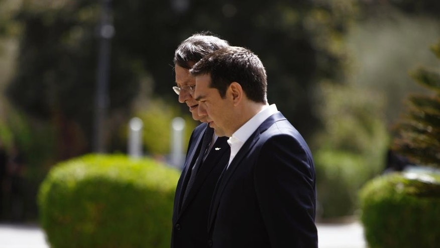 Greek Prime Minister Alexis Tsipras, front, speaks with Cyprus' President Nicos Anastasiades at the presidential palace before a meeting in capital Nicosia, Cyprus Wednesday, April, 29, 2015. Anastasiades and Tsipras are joined by Egyptian President Abdel-Fattah el-Sissi for a summit meeting on the east Mediterranean island to discuss ways of tighter economic and security cooperation between the three countries. The leaders will also discuss unfolding developments in neighboring countries including Yemen, Libya, Syria and Iraq. The meeting follows an initial summit that took place last November in Cairo, Egypt. (AP Photo/Petros Karadjias)